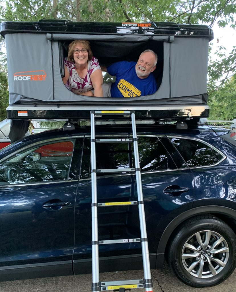 Rene and Mike live full time in the roof top tent atop a Mazda CX-9. Roofnest is the maker of their roof top tent.